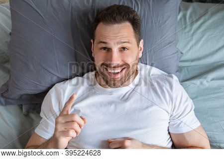 Joyful Guy Having Idea Pointing Finger Up Lying In Bed, Posing Looking At Camera In Bedroom At Home.