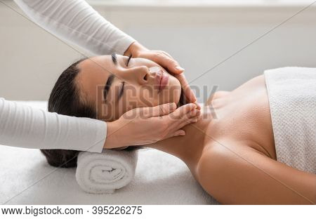 Facial Beauty Treatment. Relaxed Asian Woman Getting Professional Face Lifting Massage At Cosmetolog