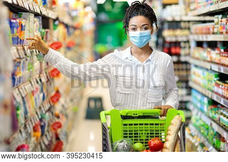 Supermarket Shopping. Black Woman Taking Food Product From Shelf Doing Grocery Shopping In Store, St