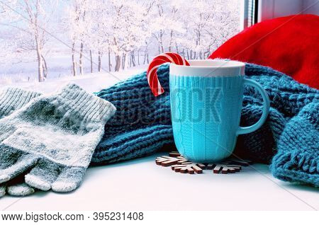 Winter Christmas background. Cup with candy cane, woolen scarf and grey gloves on windowsill and winter forest outside. Christmas background with concept of spending Christmas winter time at cozy home. Christmas composition