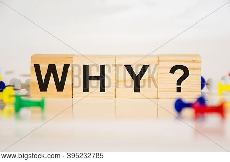The Word Why Is Written On Wood Cubes With Colored Paper Clips