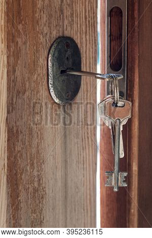 Set Of Keys On The Ring In The Keyhole In The Old Wooden Door