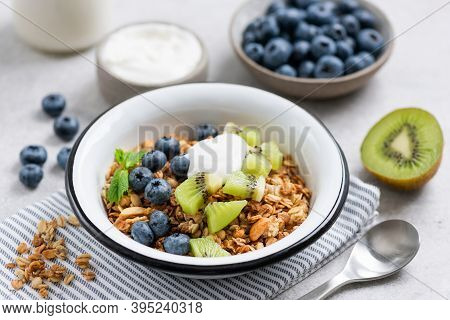 Granola With Fruits And Yogurt. Bowl Of Crunchy Oat Granola With Blueberries, Kiwi And Greek Yogurt