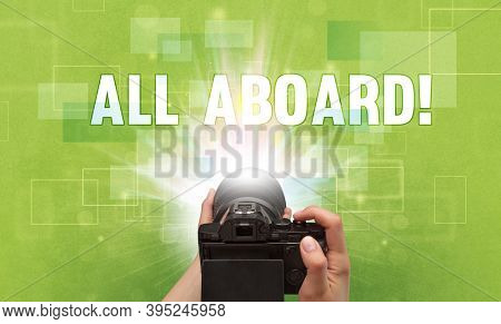 Close-up of a hand holding digital camera with ALL ABOARD! inscription, traveling concept