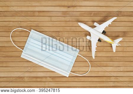 Plane Model And Face Mask On A Wooden Background With Copy Space. Resumption Of Flights. Opening Of