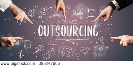 Close-Up of cropped hand pointing at OUTSOURCING inscription, modern business solution concept