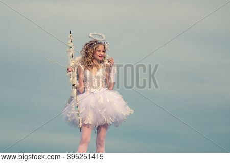 A Child In The Clothes Of An Angel On Sky Background. Cherub Girl. Concept Of Innocent Child. A Beau