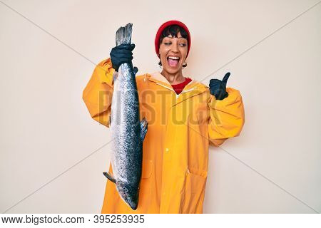 Beautiful brunettte fisher woman wearing raincoat holding fresh salmon pointing thumb up to the side smiling happy with open mouth