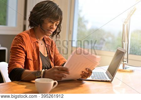 Portrait of woman entrepreneur working from home on laptop