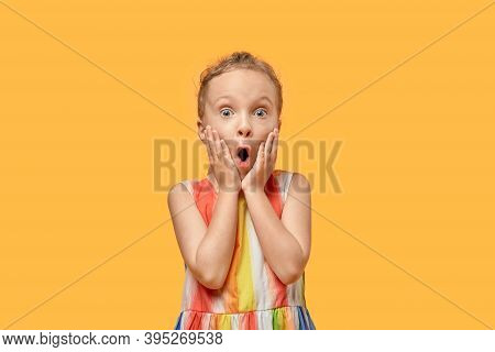 A Frightened Girl Looks At The Camera And Touches Her Face With Her Hands.