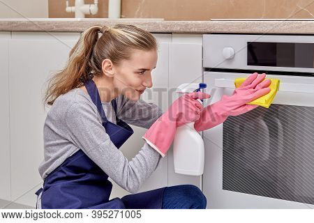 A Young Woman Cleans The Kitchen, Washes The Electric Stove With Detergent.