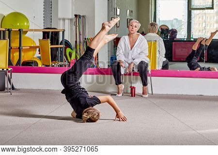 A Young Man Performs Tricks Under The Supervision Of A Teacher.