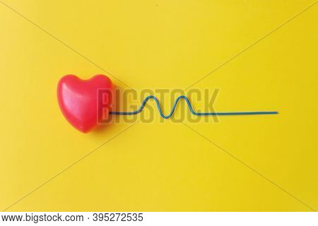 Red Heart With A Blue Curved Wire Depicting A Heartbeat. Healthy Concept. Vital Energy Concept