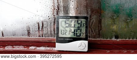 Electronic Clock, Calendar, Thermometer, And Hygrometer, Against The Background Of Condensation On G