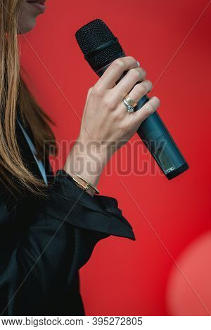 Business And Speech Topic: Woman In A Black Shirt Holding Microphone A On A Red Background