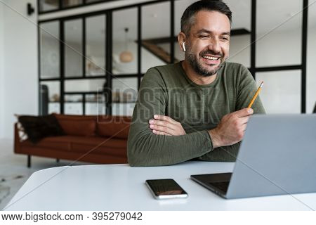 Handsome confident young businessman working in a modern office space, using laptop computer, sitting at the desk