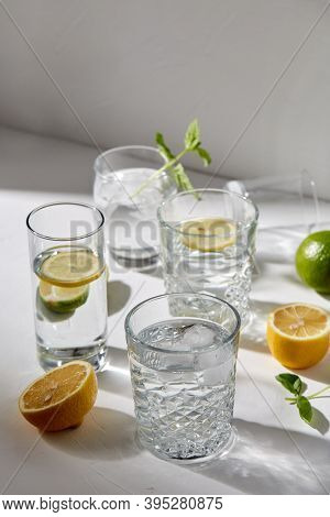 drink, detox and diet concept - glasses with fruit water or lemonade, lemons, limes and peppermint on white table