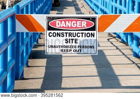 Danger Sign On Construction Gate On Pier With Blue Railings