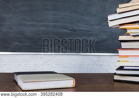 On The Background Of A School Blackboard And A Wall Made Of White Bricks, Books Are Stacked On Top O