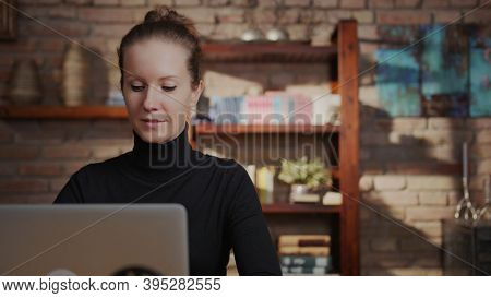 Adult woman in 30s working on laptop in home office, working from home online, using internet, thinking.