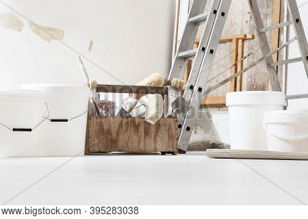 Indoor Shot Close Up Frontal View Of Bricklayer, Plasterer Or House Painter Tools On White Floor Wit