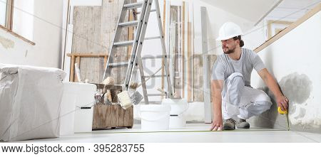 Construction Worker Plasterer Man Measuring Wall With Measure Tape In Building Site Of Home Renovati