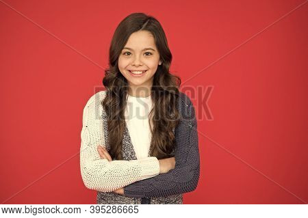 Natural Curls. Kid Cute Face Adorable Curly Hairstyle. Kid Girl Long Hair Posing Confidently. Girl C