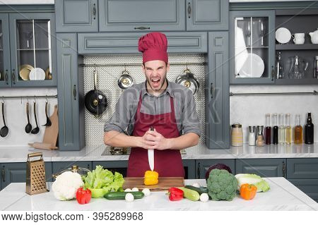 Macho In Chef Hat With Angry Face Cut Pepper With Knife In Kitchen. Cooking, Culinary, Cuisine. Vege