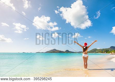 Happy Christmas Santa girl on winter south holidays cruise vacation with open arms up relaxing on Antigua Beach, Caribbean island.