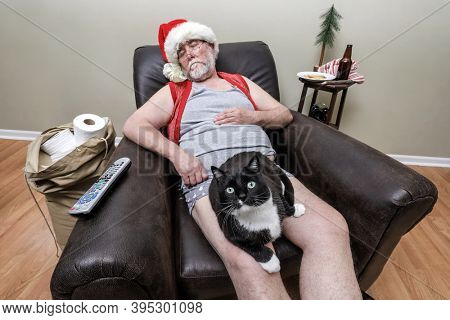 Shallow focus on cat's eyes.  Quarantine Santa Claus sleeping in an recliner with face mask and a cat on his lap