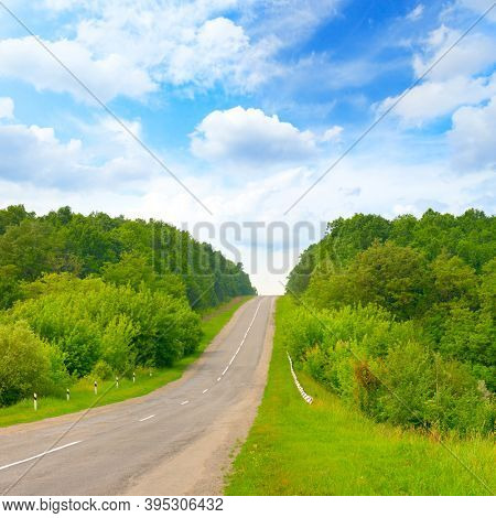 Direct road to rise in countryside with blue sky