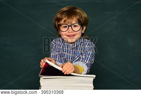 Cute Boy With Happy Face Expression Near Desk With School Supplies. First School Day. Schoolkid Or P