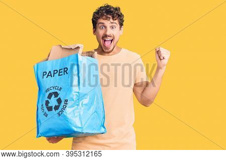 Young handsome man with curly hair holding recycling wastebasket with paper and cardboard screaming proud, celebrating victory and success very excited with raised arms