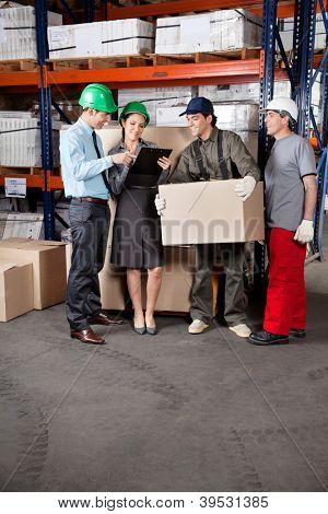 Foremen and supervisors discussing work at warehouse