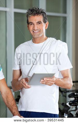 Portrait of happy mature man using digital tablet in health club