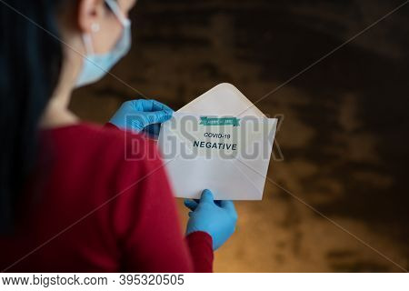 Woman Holding Negative Antigen Detection Test For Covid-19. Back View Of Woman Wearing Face Mask And