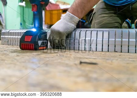 Male Employee Twists An Aluminum Profile With Slits. Production Of An Aluminum Profile According To
