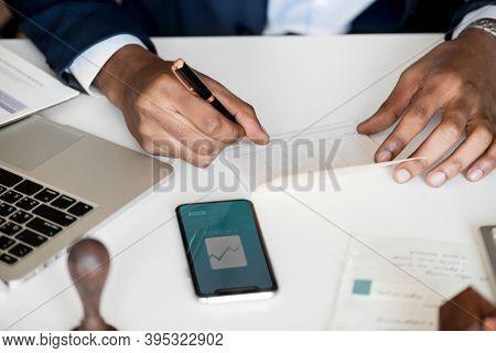 Formal businessman checking bankbook workspace