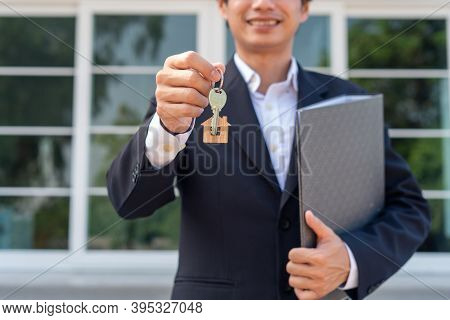 A Businessman Or Home Sales Agent Is Happily Handing The House Keys To A New Landlord. New House Mov