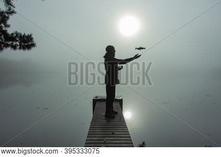 Man Playing With The Drone. Silhouette Against The Foggy Landscape.male Operating The Drone By Remot