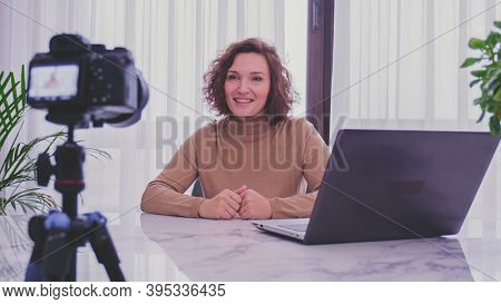 Smiling woman recording her video blog. Woman blogger videotapes her vlog at home.  Adult woman speaks in front of a video camera for her blog channel. Vlogger makes online streaming using smartphone