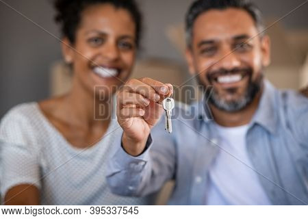Close up hands of indian man with african woman showing new home keys. Portrait of happy mixed race couple in their new house holding keys. Close up of middle eastern man with wife after moving day.