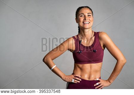 Portrait of beautiful fitness woman smiling and looking at camera isolated on grey background. Mid woman in sportswear relaxing after training at gym. Happy fit girl on gray wall with copy space.