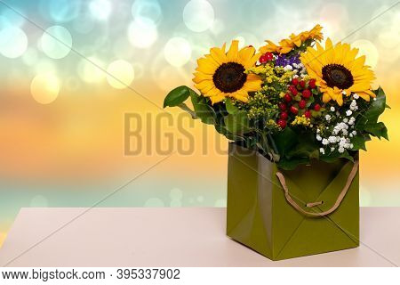 Closeup Of A Beautiful Bouquet With Yellow Sunflowers In A Decorative Green Gift Box On A Yellow Tab