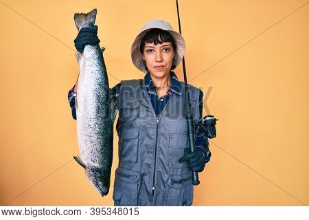 Beautiful brunettte fisher woman holding fishing rod and raw salmon relaxed with serious expression on face. simple and natural looking at the camera.