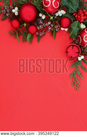 Christmas background border with red ball baubles & winter greenery of holly, ivy, mistletoe. Festive composition for the holiday season. Flat lay, top view, copy space.