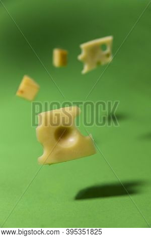 Levitation Background. Chunks Of Cheese With Holes Floating In The Air. Yellow Pieces Of Cheese Fall