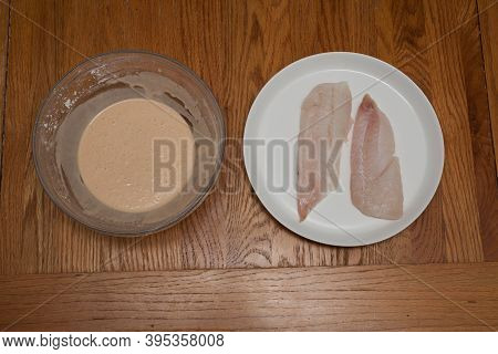 Two Raw Haddock Fillets Next To A Bowl Of Beer Batter