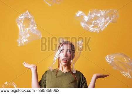 Young Woman Overwhelmed By Plastic Waste And Suffocating From Plastic Bag Over Her Head - Ecology An