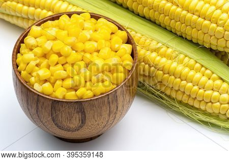 Sweet Corn Grains In Wooden Bowl On The Background Of Fresh Corn Cobs. Fresh Sweet Corn Top View.